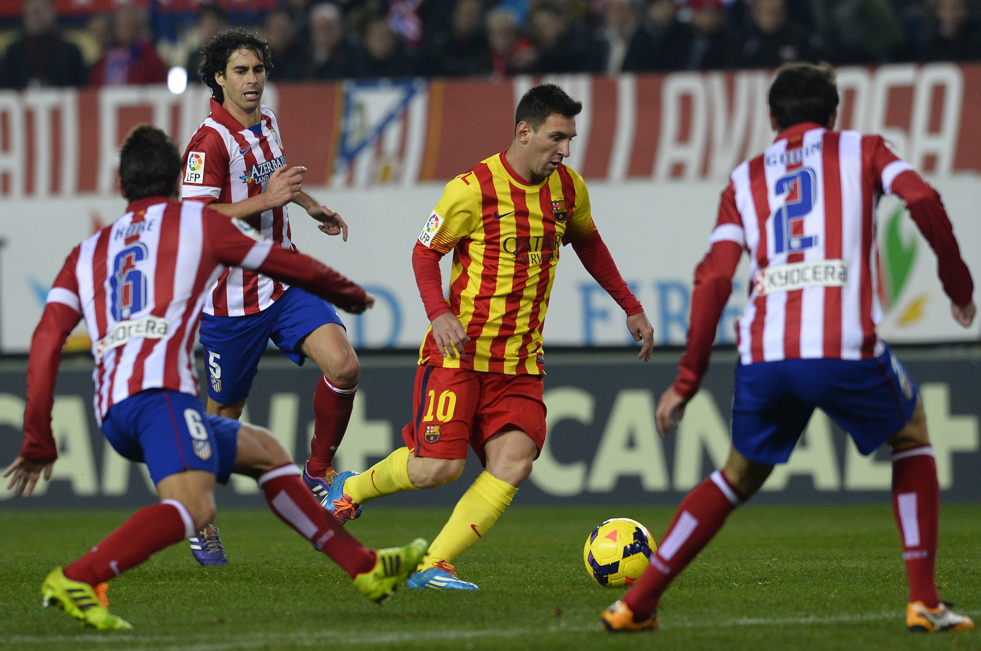 Barcelona's Argentinian forward Lionel Messi (2ndR) vies with Atletico Madrid's Portuguese midfielder Tiago Mendes (FarL) during the during the Spanish league football match Club Atletico de Madrid vs FC Barcelona at the Vicente Calderon stadium in Madrid on January 11, 2014.  AFP PHOTO/ GERARD JULIEN        (Photo credit should read GERARD JULIEN/AFP/Getty Images)