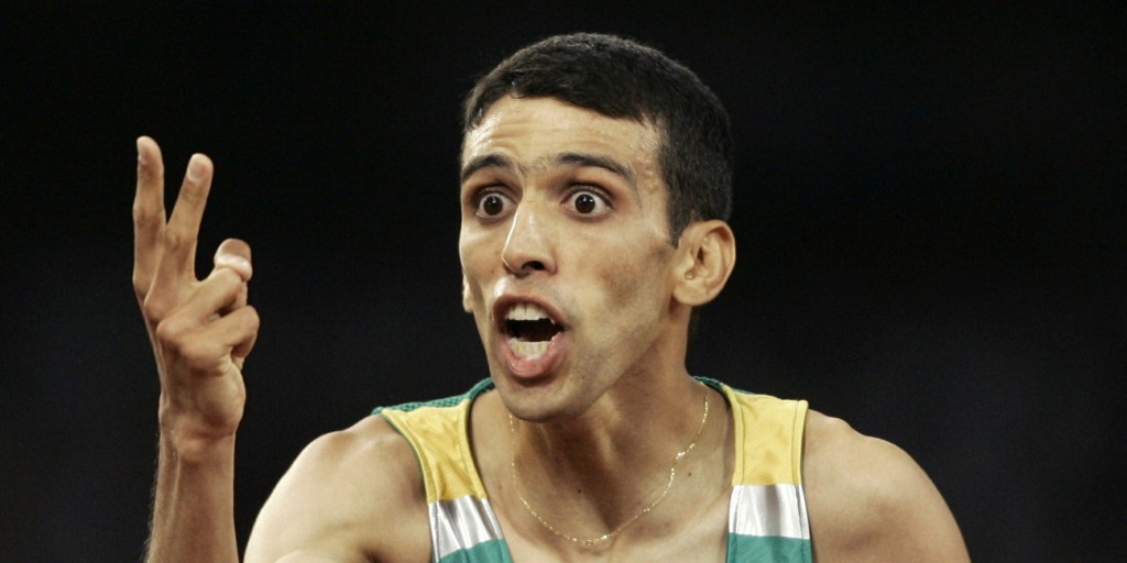 Morocco's Hicham El Guerrouj celebrates his two gold medals after winning the men's 5,000 metres final at the Athens 2004 Olympic Games August 28, 2004. Morocco's Hicham El Guerrouj won the gold medal in a time of 13 minutes 14.39 seconds ahead of Ethiopia's Kenenisa Bekele and Kenya's Eliud Kipchoge.El Guerrouj also took gold in the men's 1,500 metres. REUTERS/Dylan Martinez